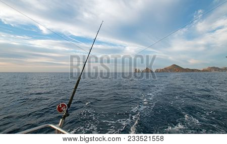 Fishing rod on charter fishing boat on the Sea of Cortes / Gulf of California viewing Lands End at Cabo San Lucas Baja Mexico BCS stock photo