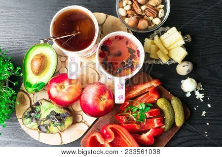 English health breakfast for two, quail eggs and fresh vegetables, cheese, nuts, avokado, sandwich with avokado and basil and fruit, black tea cups stock photo