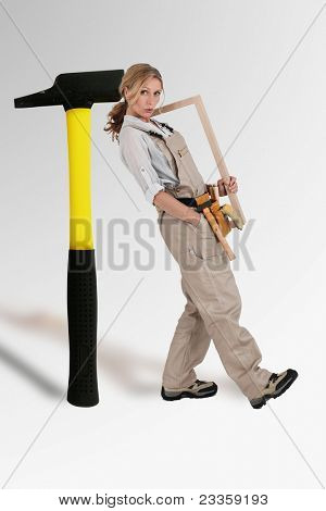 craftswoman leaning on a mega hammer stock photo