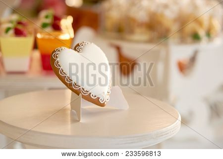 Close-up of a delicious heart-shaped glazed cookie standing on the wooden stand near the candybar with different desserts like yellow cupcakes and red jellies. festive choice gor wedding celebration. stock photo