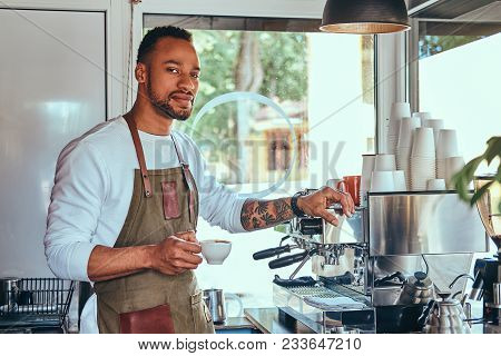 African-American barista making a coffee with the professional coffee machine, at the coffee shop. stock photo