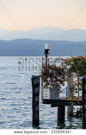 Impression of a sunny afternoon at a landing pier in Sirmione at Lake Garda, Italy stock photo