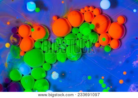 Red and green neon colorful paint bubbles. Fluorescent ink in water in ultraviolet light. Color abstract background stock photo