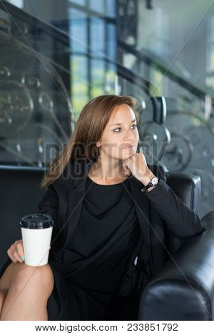 Closeup portrait of relaxed young beautiful brown-haired woman looking away, holding disposable cup and sitting on sofa in hotel lobby. Coffee break concept. Front view. stock photo