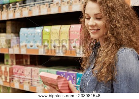 Horizontal portrait of deligted beautiful young female with curly hair reads with satisfied expression information about product, chooses something in supermarket. People and buying concept. stock photo