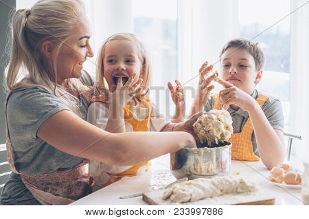 Beautiful blond mom teaching her two children cooking on the kitchen. Parent making everyday breakfa