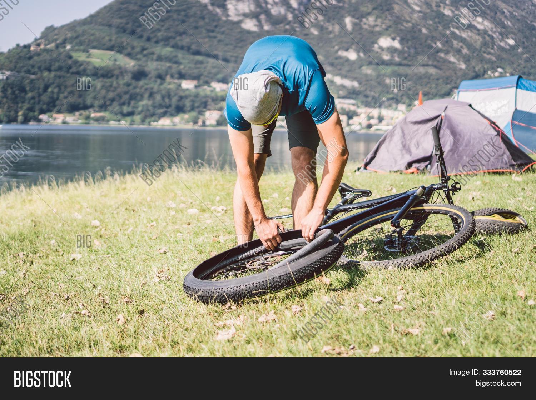Bike Repair. Man Repairing Mountain Bike. Cyclist Man In Trouble Rear Wheel Wheel Case Of Accident.