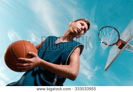 Sports and basketball. A young teenager in a black tracksuit stands with a ball in his hands and prepares to throw the ball into the ring. Blue sky. Bottom view stock photo