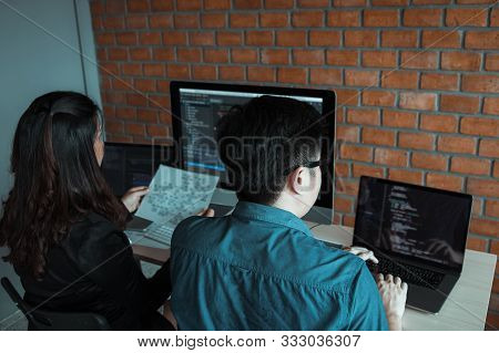 Two Software Developers Are Using Computers To Work Together With Their Partner At The Office Desk.