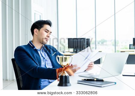 asian young businessman have stressed see a the document  business plan and a champion cup,laptop computer on wooden table after business losses In the office room background. stock photo