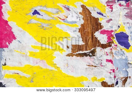 Collage of colourful torn magazine paper glued on rough surface. Grungy street billboard with motley ripped and peeling posters texture background. stock photo