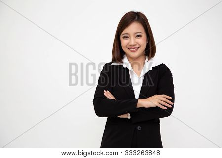 Portrait of successful business asian women in black suit with arms crossed and smile isolated over white background, Young businesswoman smiling and looking at camera, Happy feeling concept stock photo