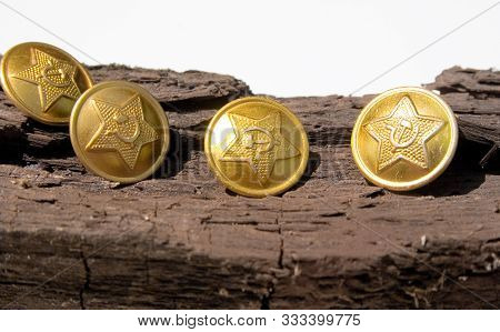 Buttons with the symbols of the USSR. Four yellow button of a military clothes of the USSR period with a star, a sickle and a hammer on old wooden bar stock photo