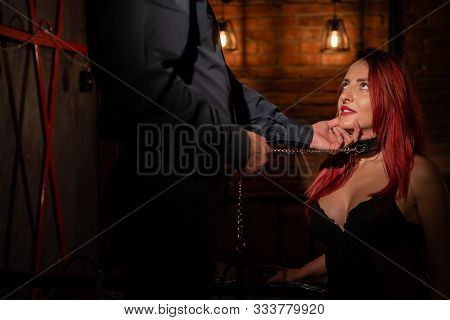 Leather belt on the neck of BDSM. Luxurious chest in black underwear. A woman kneels in front of her partner in sexual games as a victim. Toys for adults. Finger in the mouth. stock photo