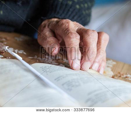 Old woman hand on the open prayer book (Christian prayer book in Ukrainian). Reading the book. Praying. stock photo