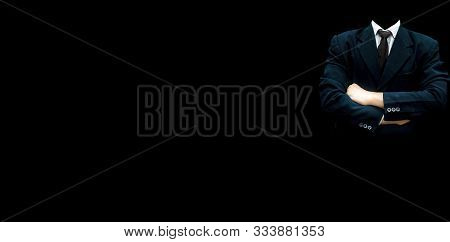 Faceless unrecognizable male wearing a blue colored suit with a black necktie and standing against a black background with good positive attitude. Wide-angle full resolution image. stock photo