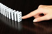 Hand pushing dominoes on wooden foundation