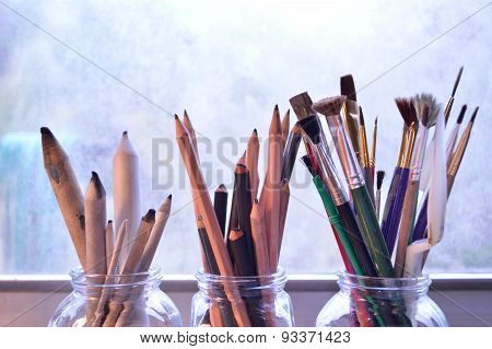 Paintingdrawing and sketching tools. Graphite and charcoal pencils for fine art in the middle and blending stumps or tortillons for blending pencil drawings to the left. Bouquet of colorful brushes of different types and sizes to the right. ** Note: Shall stock photo