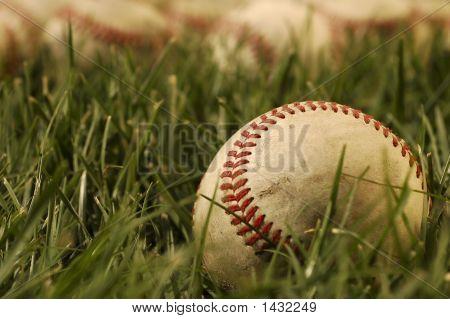 Nostalgic baseballs in the grass on a baseball field stock photo