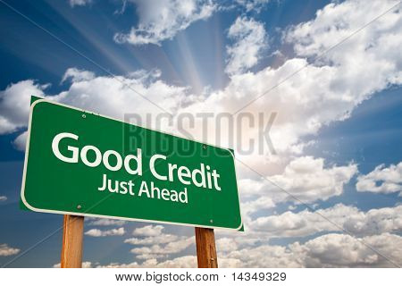 Good Credit Green Road Sign with Dramatic Clouds, Sun Rays and Sky. stock photo