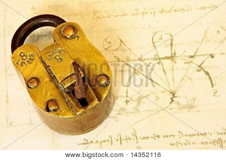 Antique brass padlock, on a page of Da Vinci's writings.  19th Century vintage Indian padlock. stock photo