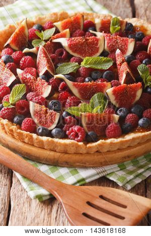 Delicious pastry: tart with fresh figs raspberries and blueberries close-up on the table. Vertical stock photo