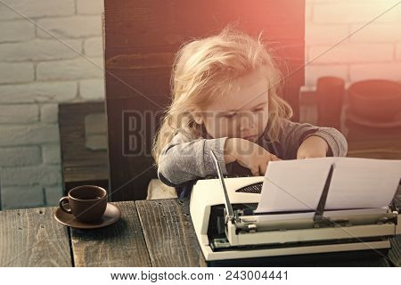 Happy kid having fun. small boy or businessman child sitting at table and typing typewriter with paper and coffee cup on white brick wall background, business and new technology stock photo