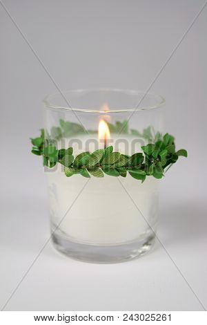 A lit white glass votive candle with a green boxwood accent. stock photo