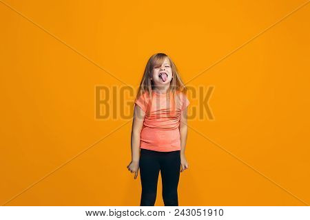 I lost my mind. The teen girl with weird expression. Beautiful female half-length portrait isolated on orange studio backgroud. The crazy teenager. The human emotions, facial expression concept. stock photo