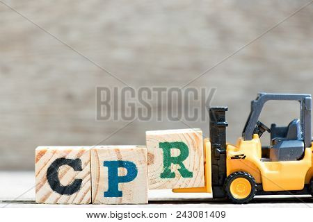 Toy forklift hold letter block R in word CPR (abbreviation of Cardiopulmonary resuscitation) on wood background stock photo