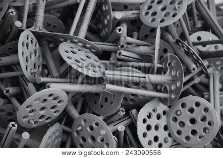 Background pattern of many gray plastic dowels fastening for thermal insulation. A huge pile of fixtures for the installation of expanded polystyrene plates for the insulation of the building walls stock photo