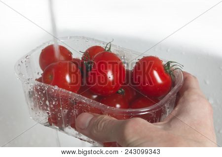 The male hand holds a transparent box of red cherry tomatoes under a trickle of water. Transparent box with tomatoes and a trickle of water in the washbasin. Hand holds a box with red cherry tomatoes under the tap in the washbasin. stock photo