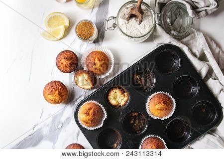 Fresh baked homemade lemon cakes muffins standing in teflon baking dish with eucalyptus branch, linen cloth and ingredients in glass jars above over white marble texture background. Flat lay, space stock photo