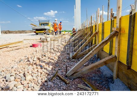 Long wooden mold is assembled and ready for concreting base of edifice wall. stock photo