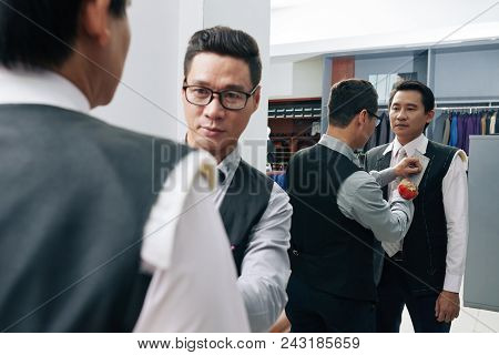 Professional Vietnamese tailor making chalk marks on acking during first fitting stock photo