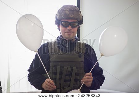 Smiling Military at bulletproof vest, body armor covers and helmet with balloons stock photo