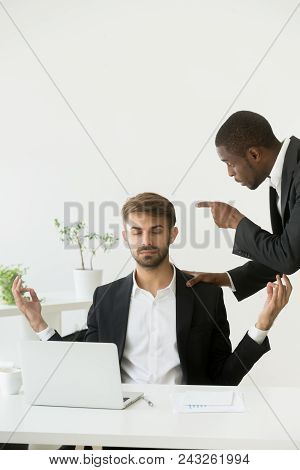 Calm funny Caucasian worker meditating, practicing yoga while African American boss shouting at him, teaching, blaming for failure. Concept of emotions control, stress relief, balance stock photo