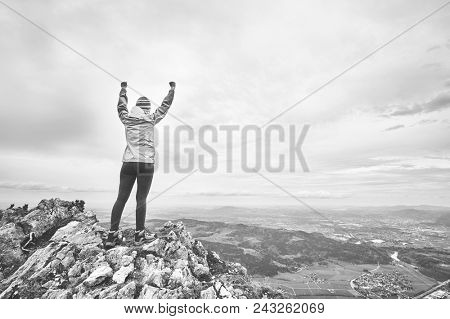 Black and white portrait of young female hiker with arms raised celebrating achievement standing on top of mountain after successful ascent - adventure, freedom or success concept stock photo