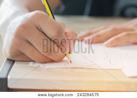 Education test concept : Man Hands high school, university student holding pencil for testing exams writing answer sheet and exercise for taking in exam paper on wood table at classroom with uniform stock photo