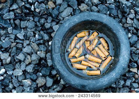 Amount of cigarettes butt in a gray motar with water, put on gray small stone stop smoking and get off cigaret idea concept, free from nicotine ,make a better life and healthy for everybody. stock photo