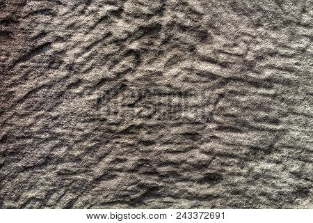 Polished stone texture photo. Natural stone background. Weathered rock relief. Old building stone wall surface closeup. Distressed stone texture. Solid construction material. Grungy rock formation stock photo