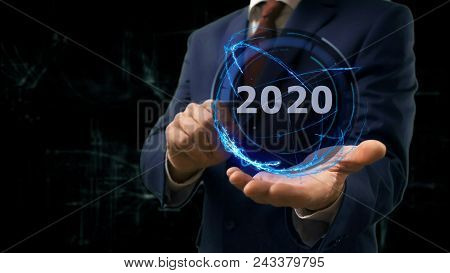 Businessman shows concept hologram 2020 on his hand. Man in business suit with future technology screen and modern cosmic background stock photo