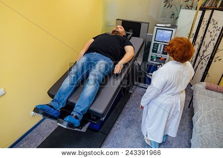 Doctor and male patient at non-surgical treatment of cervical and thoracic spine in medical center. stock photo