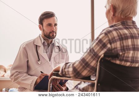Handsome old man is talking with a doctor while sitting in hospital ward stock photo