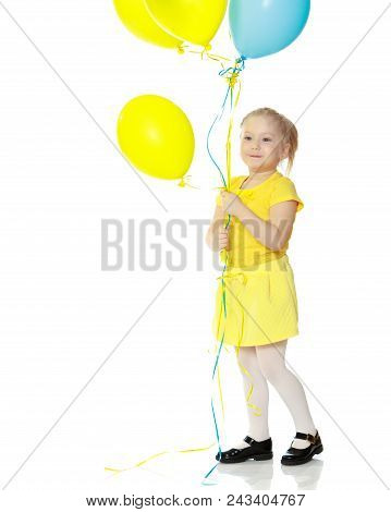 A lovely little round-faced blonde girl, with very long beautiful hair, in short skirts and yellow jerseys.She holds balloons in her hand.Isolated on white background. stock photo