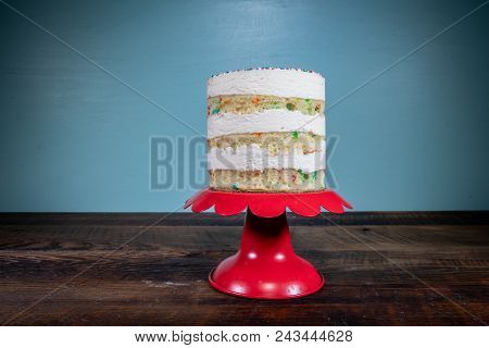 Three Tiered Naked Funfetti Cake On Red Cake Stand Centered stock photo