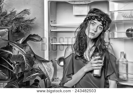 Woman dressed in boho style looks skinny. Lady on dreamy face stands in front of opened empty fridge and drinks milk. Dieting concept. Girl cares about weight. Lady slim and skinny holds glass. stock photo