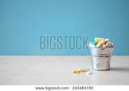Assorted pharmaceutical medicine pills, tablets and capsules in the bucket over blue background. Pharmaceuticals antibiotics pills medicine, different colorful antibacterials drugs. Copy space stock photo