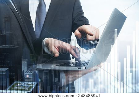 Businesspeople pointing at laptop screen on city background with business chart. Finance and teamwork concept. Double exposure stock photo