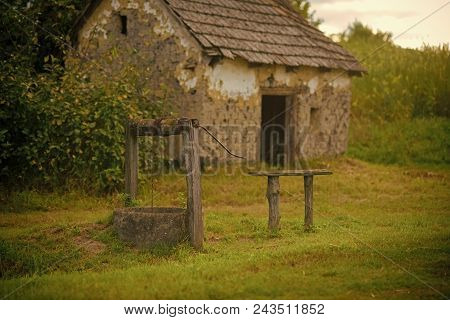 Village with abandoned building. House barrack with old well in yard. Rural lifestyle, countryside. Decay, decline, ruins. Architecture, structure construction stock photo